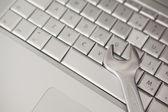 Pliers lying on silver keyboard — Stock Photo