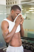 Fit man wiping sweat after workout in gym — Stok fotoğraf