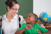 Pupil and teacher smiling at each other — Stock Photo