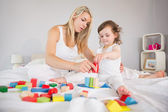 Mother and daughter playing with building blocks on bed — Foto de Stock