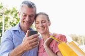 Szczęśliwa para starszy patrząc smartphone gospodarstwa torby na zakupy — Zdjęcie stockowe