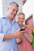 Happy senior couple looking at smartphone holding shopping bags — Photo