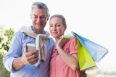 Happy senior couple looking at smartphone holding shopping bags — Stok fotoğraf
