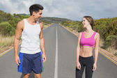 Fit couple standing on the open road — Stock Photo