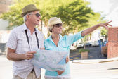 Happy tourist couple using map in the city — Foto de Stock