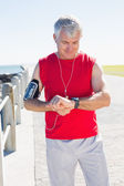 Fit mature man checking the time on the pier — Stock Photo