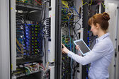 Technician using tablet pc while analysing server — Stock Photo