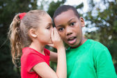 Cute children sharing gossip outside — Stock Photo