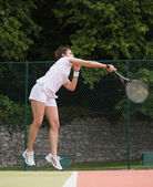 Pretty tennis player jumping and hitting — Stock Photo