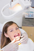 Dentist putting mouth retractor on girl — Stockfoto