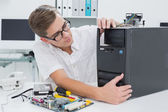 Young technician working on broken computer — Stock Photo