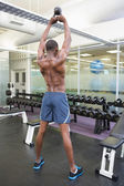 Muscular man lifting kettle bell — Stok fotoğraf