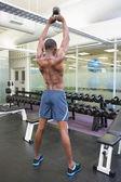 Muscular man lifting kettle bell — Stockfoto
