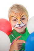 Happy little boy in tiger face paint with balloons — Stock Photo