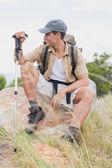 Hiking man sitting on mountain terrain — Stock Photo