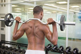 Shirtless man lifting barbell in gym — Stock Photo