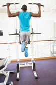 Muscular man doing pull ups at gym — Foto Stock