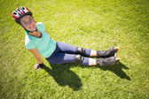 Fit mature woman in roller blades on the grass — Stockfoto