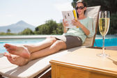 Woman reading book by pool with champagne in foreground — Stock Photo