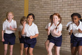 Cute pupils warming up in PE uniform — Stock Photo