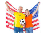 Football fan couple cheering and smiling at camera — Stockfoto