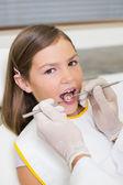 Dentist examining a little girls teeth — Stock Photo