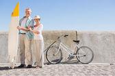 Happy senior couple posing with surfboard — Stock Photo