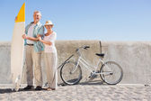 Happy senior couple posing with surfboard — Stock Photo