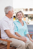 Happy mature couple sitting on bench in the city — Stock Photo
