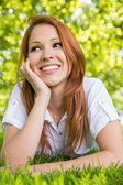 Pretty redhead relaxing in the park  — Photo