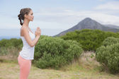 Woman with hands joined standing on countryside landscape — Stock Photo