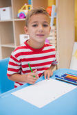 Cute little boy drawing at desk — Photo
