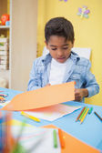 Little boy cutting paper shapes — Stock Photo