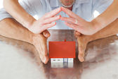 Couple sheltering miniature house with hands — Stock Photo