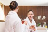 Smiling women in bathrobes having tea — Стоковое фото