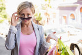 Happy mature woman smiling at camera with her shopping purchases — Stock Photo