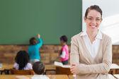 Pretty teacher at back of classroom — Stock Photo