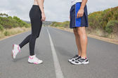 Side view low section of fit couple standing on road — Stockfoto