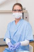 Dentist in blue scrubs holding dental tools — Stock Photo