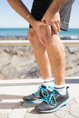 Fit man gripping his injured knee — Stock Photo