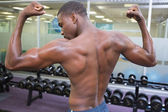 Muscular man flexing muscles in gym — Photo