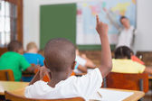 Pupil raising hand in classroom — Stock Photo