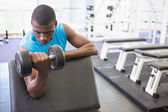 Man exercising with dumbbell in gym — Stockfoto