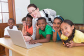 Teacher and pupils working at laptop — Stock Photo