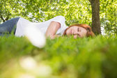 Pretty redhead lying on the grass — Stock Photo