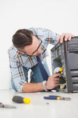 Computer engineer working on broken console with screwdriver — Stock Photo