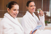 Women in bathrobes drinking water and text messaging — Stock Photo