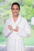 Beautiful woman in bathrobe having tea outdoors — Stockfoto