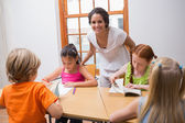 Teacher standing with pupils at desk — Stock Photo