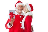 Festive couple embracing and holding gift — Стоковое фото